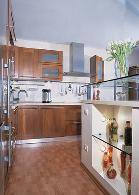 Кухонный фартук выложен плиткой под мозаику белого цвета.  На таком фоне особенно выразительно смотрится рейлинговая система, позволяющая эффективно использовать пространство между верхними и нижними модулями  и держать  под рукой разнообразные аксессуары