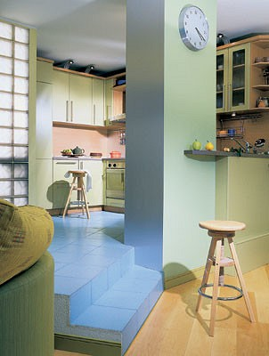 Просторная кухня отчасти слилась  со столовой.  Их разделила невысокая барная стойка  с колонной и две ступеньки,  но все же это две вполне самостоятельные зоны