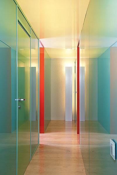 Все детали пространства словно стараются слиться с поверхностью стен: встроенные с ними заподлицо двери,  плоская колонна светильника из матового белого стекла