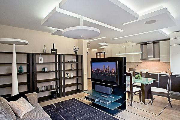 Три светящихся куба в кухне над барной стойкой<nbsp/>- светильники De Majo Illuminazione, а также необычные, воспринимающиеся как некие скульптурные композиции светильники Equilibre S5 и Equilibre F3 (Prandina) в гостиной дополняют геометрические формы подшивной конструкции потолка