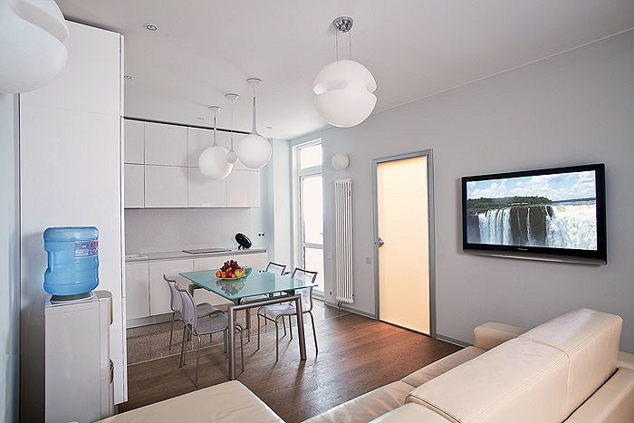 Настроение и ритм в кухне-гостиной задают потолочные светильники Lucialternative в форме шаров, символизирующие небесные светила. Акцент на осветительных приборах далее прослеживается во всех помещениях, но там они имеют правильную геометрическую форму