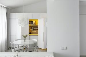 Квартира архитекторов: белый интерьер с кухней в шкафу и спальней на антресоли