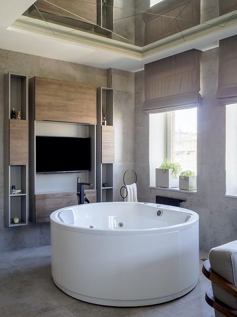 Круглая ванна в спа-зоне стоит п...