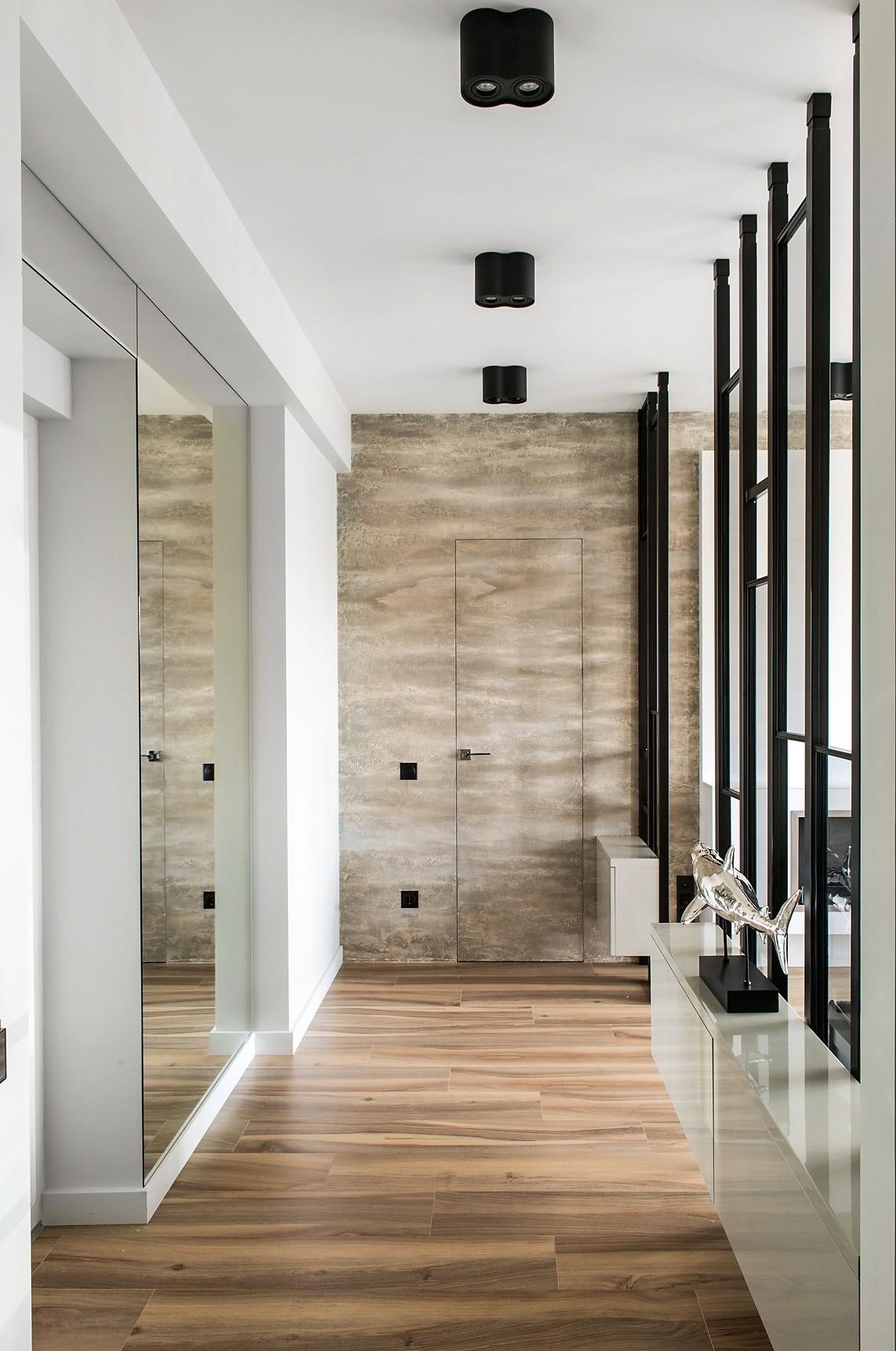 Торцевая стена прихожей, она же главная стена гостиной, отделана покрытием под бетон и совсем незаметно прорезана двумя дверьми-невидимками (в спальню и в гардеробную)