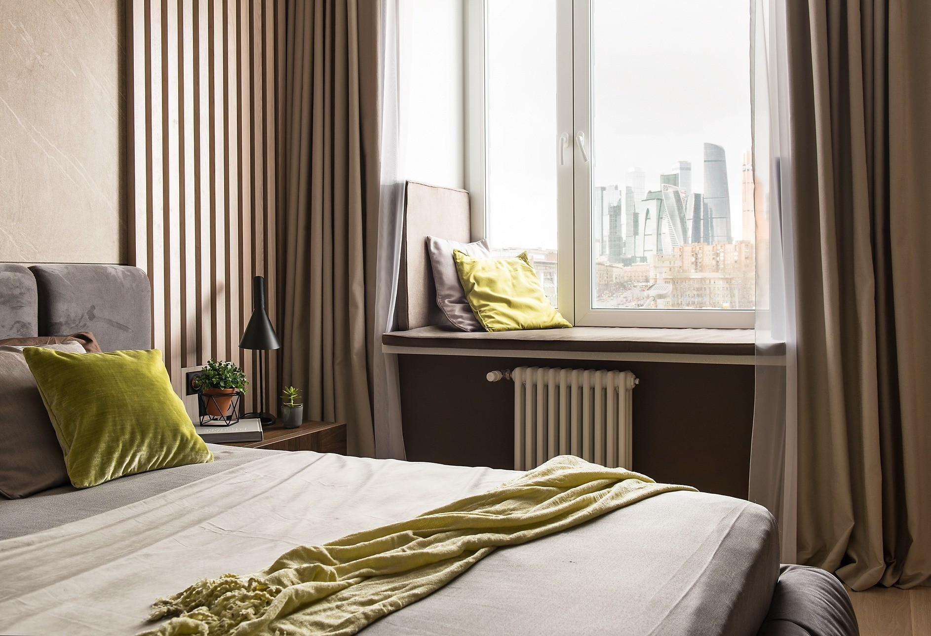 В спальне два типа штор, хотя обычно они раздвинуты. Широкий подоконник изискусственного камня  с успехом заменил кушетку, для удобного  отдыха его снабдили подушками