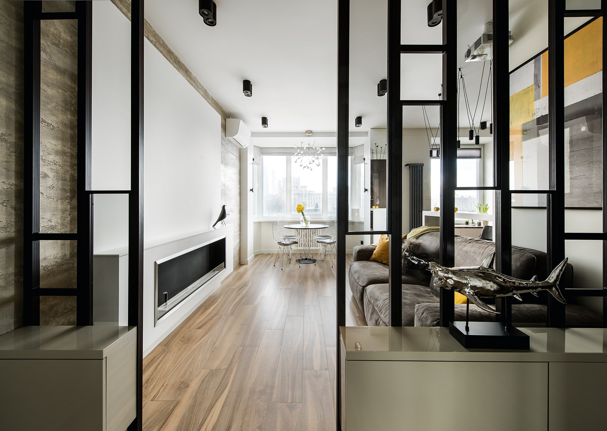 Раскладной диван в гостиной может служить спальным местом. Пол встудии облицован плиткой под дерево ― красиво ипрактично