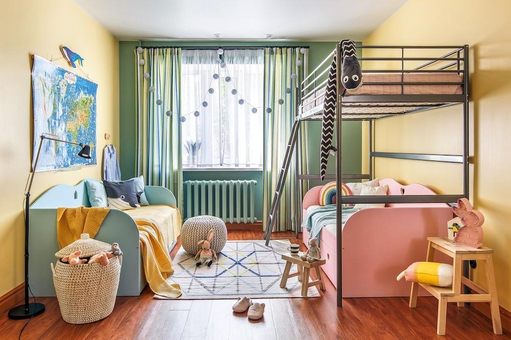 Совместное пространство для разнополых детей визуально поделили с помощью разной по цвету мебели и аксессуаров. Старшую дочь поселили на верхнем этаже кровати-чердака, младшую девочку — н...