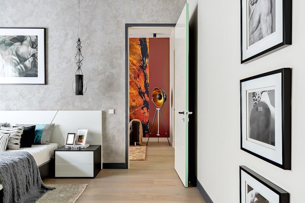 В спальне потолококрашен вцвет графита, стена заизголовьем имитирует поверхность сырого бетона, на стенах чёрно-белые фото