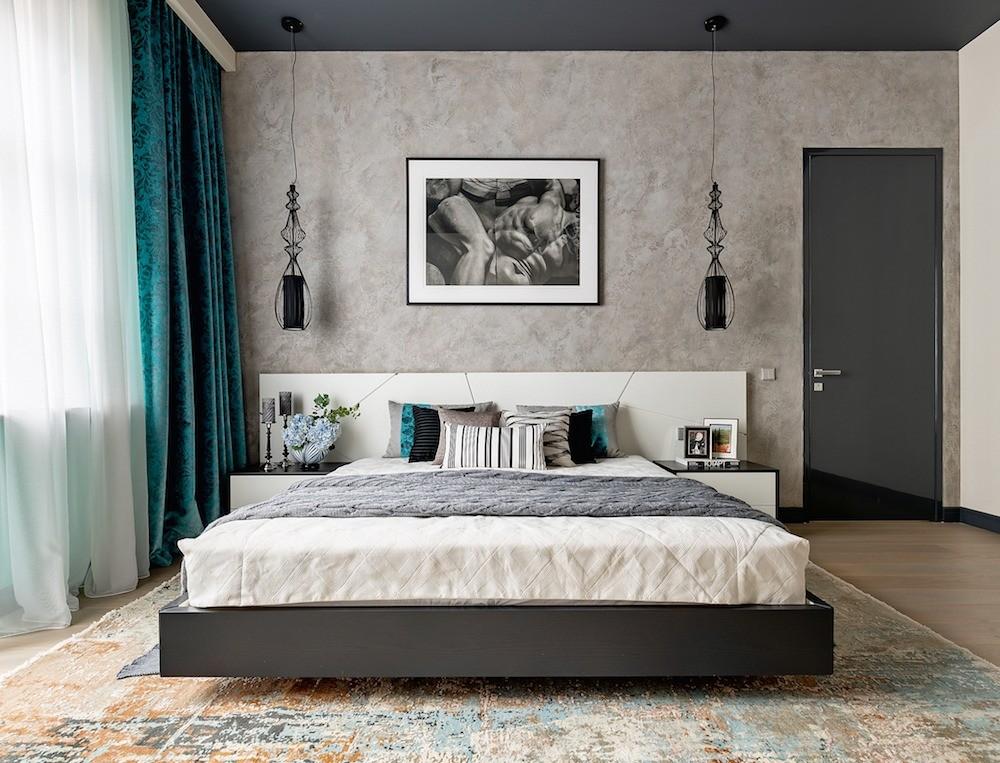 Спальня почти ахроматична, но палитру обогащают бирюзового оттенка стена и занавесь, обрамляющая окно, — цвет волн Средиземного моря умиротворяет