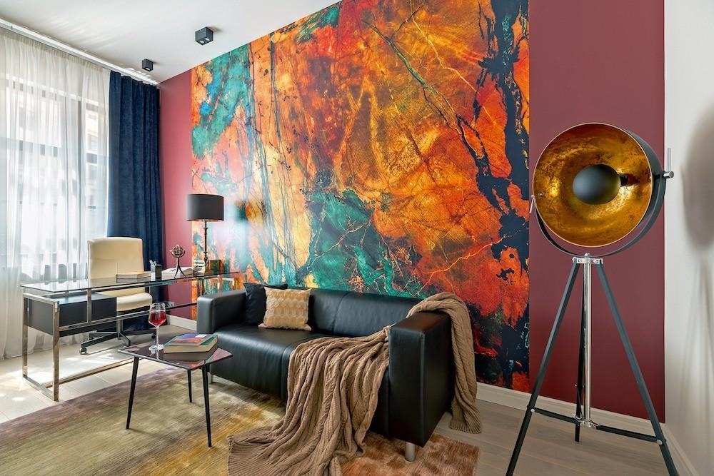 Взрывной дизайн кабинета стимулирует ктворчеству. Втоже время эта комната может служить малой гостиной: удобный диван скожаной обивкой, журнальный стол располагают к общению зачашкой...