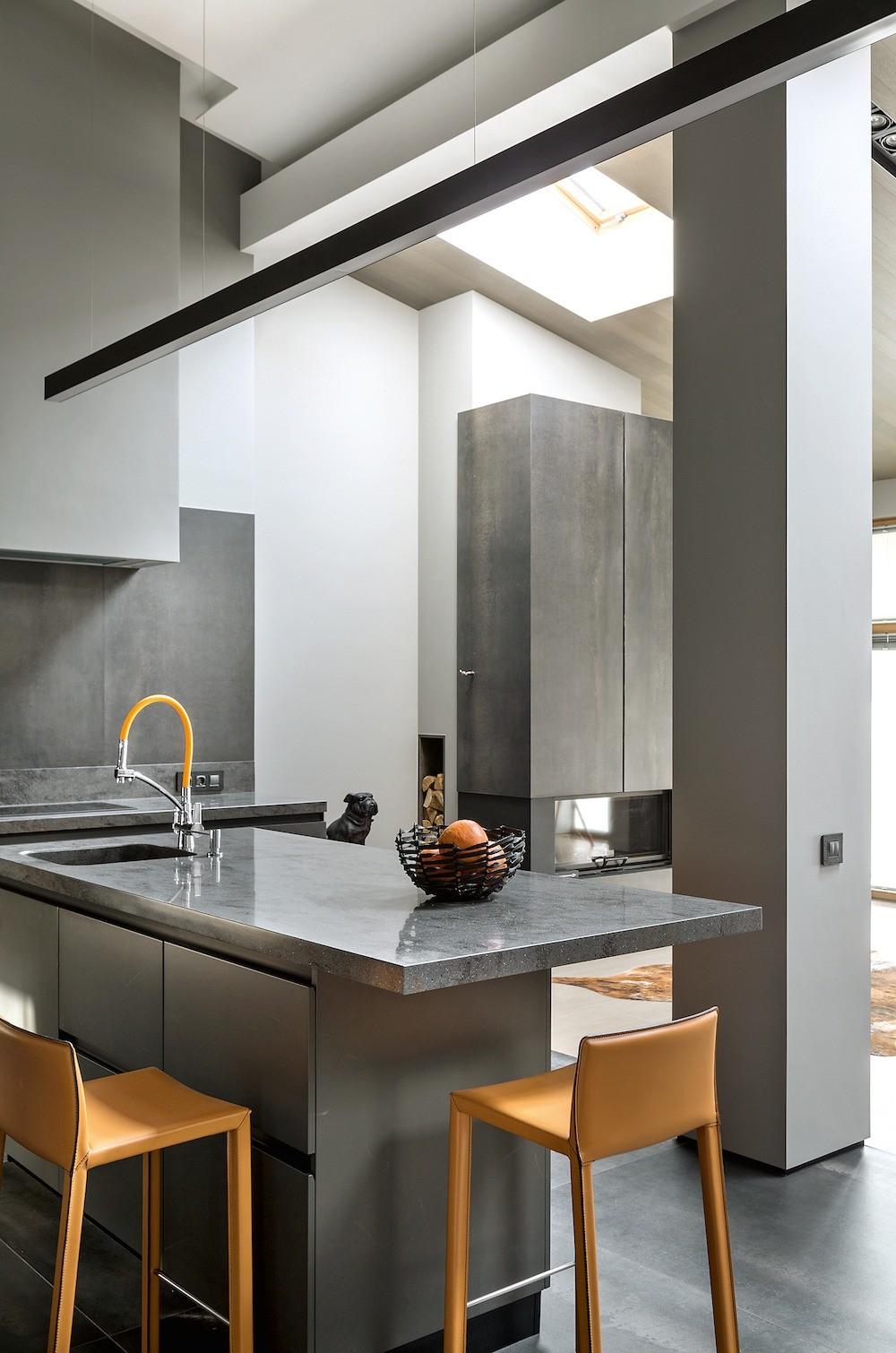 Рабочий остров кухни полубарной высоты служит и местом для завтраков. Практичная столешница из кориана с широким свесом позволяет удобно устроиться за столом.