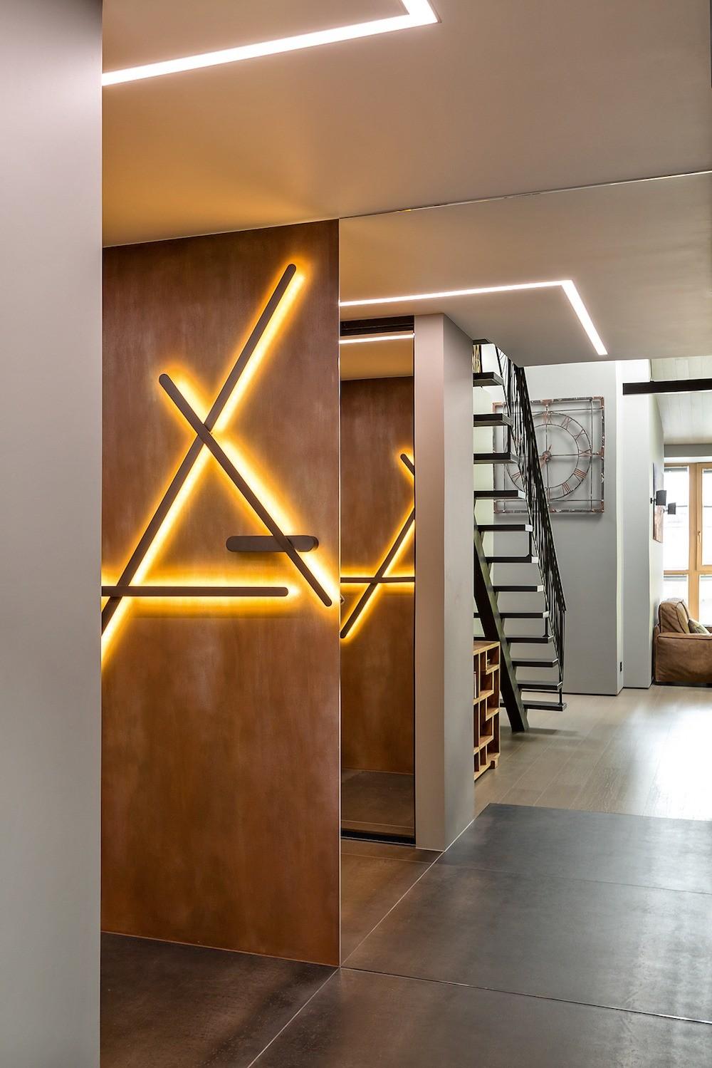 В проходных зонах с невысокими потолками освещение обеспечивают встроенные линейные светильники в алюминиевых корпусах. Оригинальный  настенный светильник выглядит как арт-объект.