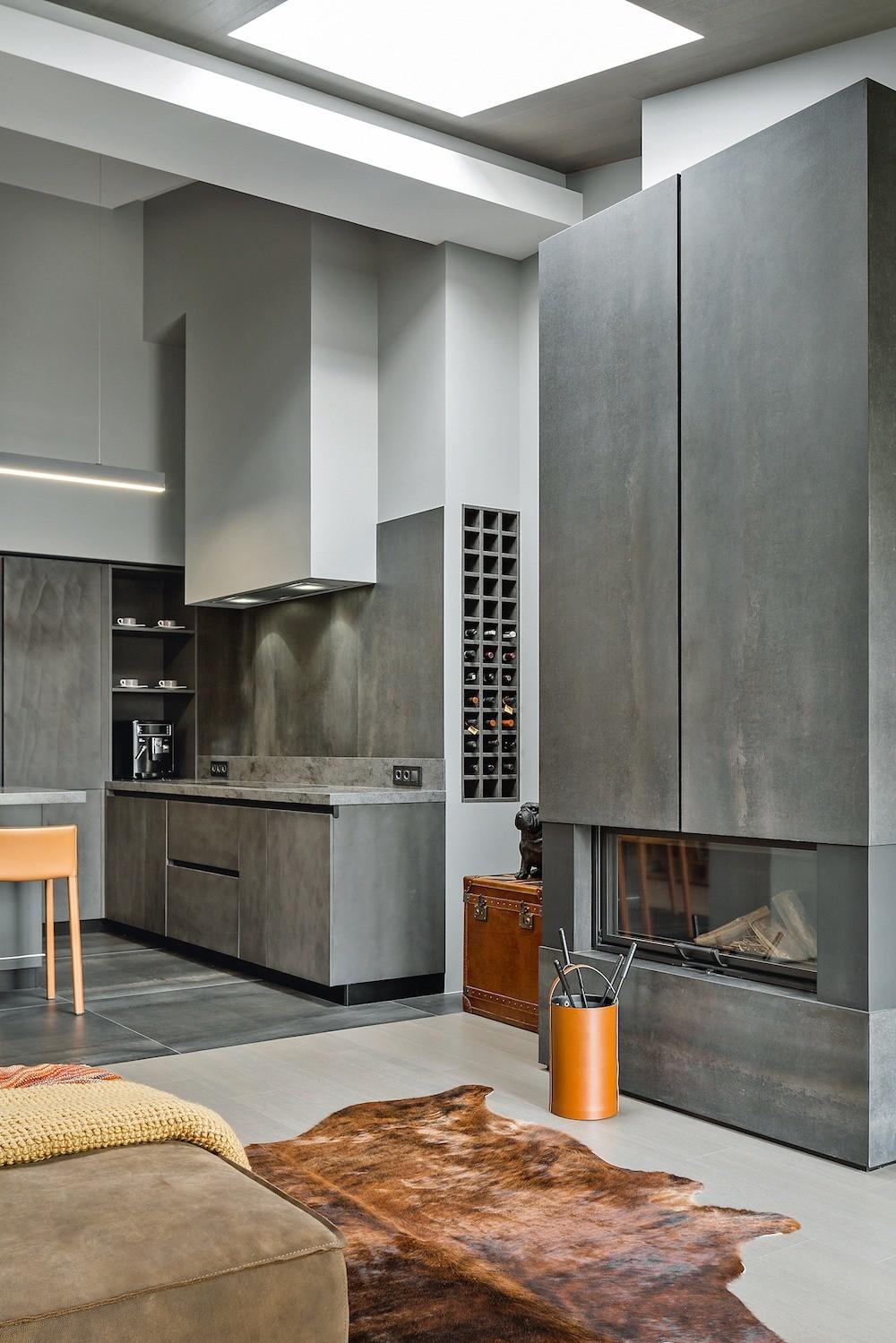 Высокий (0,15 м) цоколь кухонных модулей позволил оборудовать внём места для хранения.  Камин облицевали крупноформатными керамогранитными плитами.