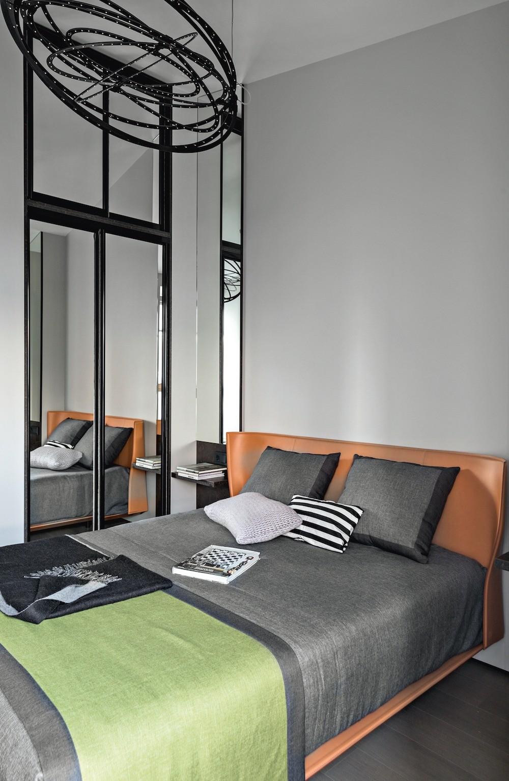 Небольшую спальню оптически расширили зеркальные двери встроенного шкафа, а оригинальным дополнением кигре отражений стало узкое зеркало надприкроватной тумбочкой.