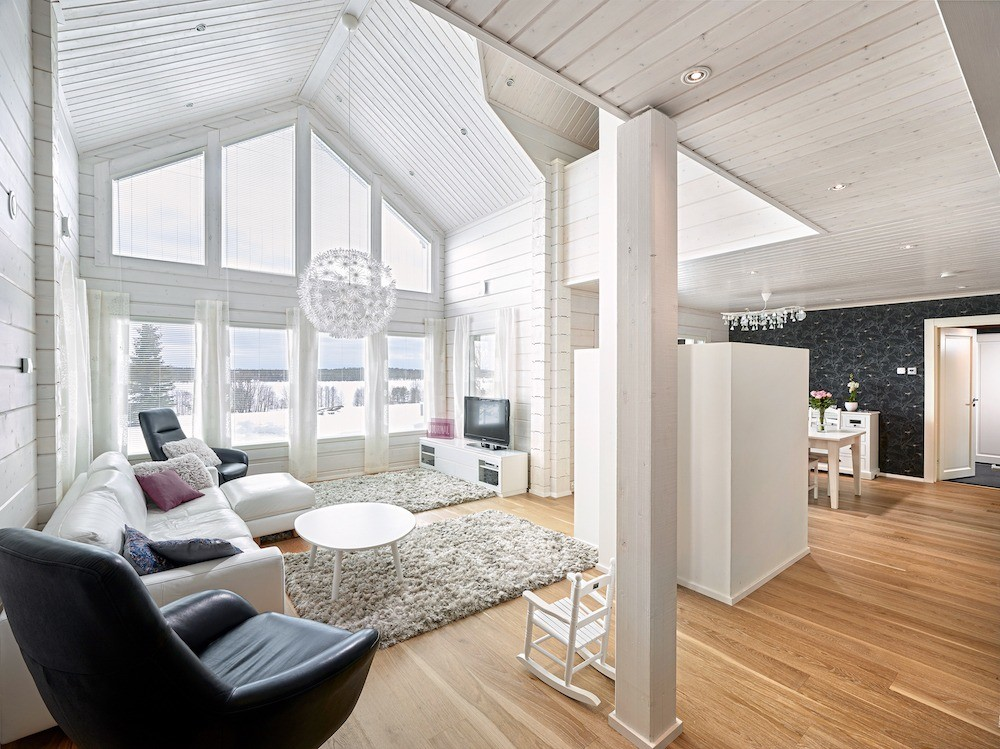 Регулировать интенсивность естественного освещения в помещениях первого этажа помогают горизонтальные жалюзи. В зоне гостиной нижний ряд окон дополнен полупрозрачными драпировками