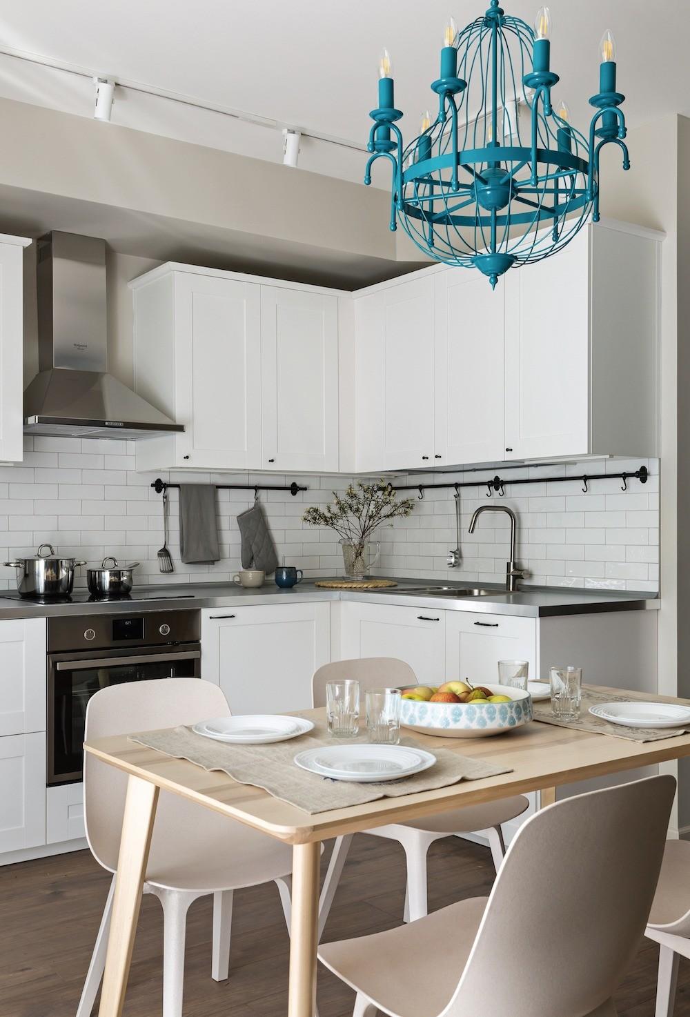 Трековая система повторяет напотолке контур кухонной композиции иобеспечивает хорошую освещённость врабочей зоне спомощью направленных светильников
