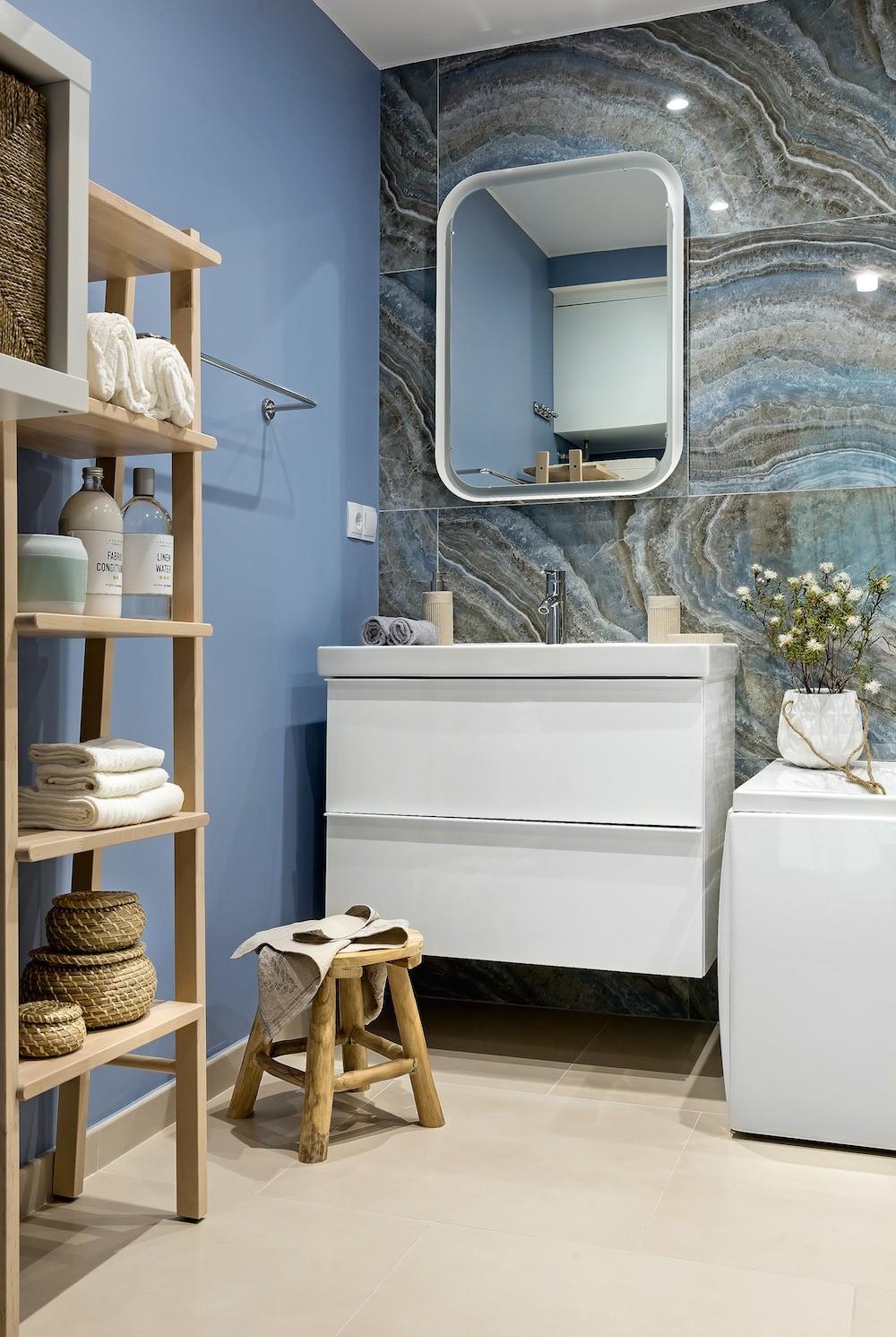 Стены ванной окрашены в голубой цвет, выгодно подчеркнувший отделку стены взоне умывальника красивой плиткой с великолепной текстурой под природный камень