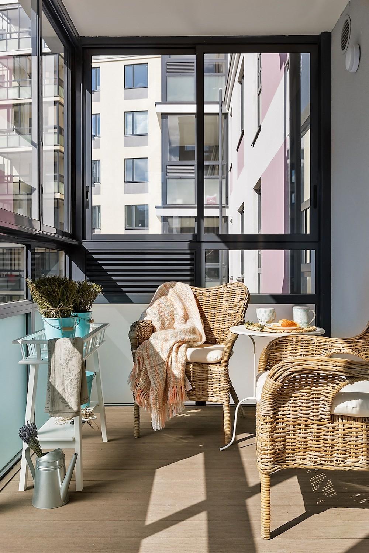 На остеклённом балконе установили лёгкие плетёные кресла и компактные подставки-консоли, чтопридало зоне летний вид