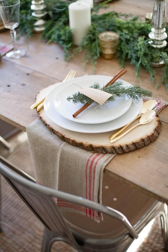 Деревянный стол без скатерти, льняные салфетки, круглые срезы дерева и еловые ветки. Очень современно, модно и уютно.