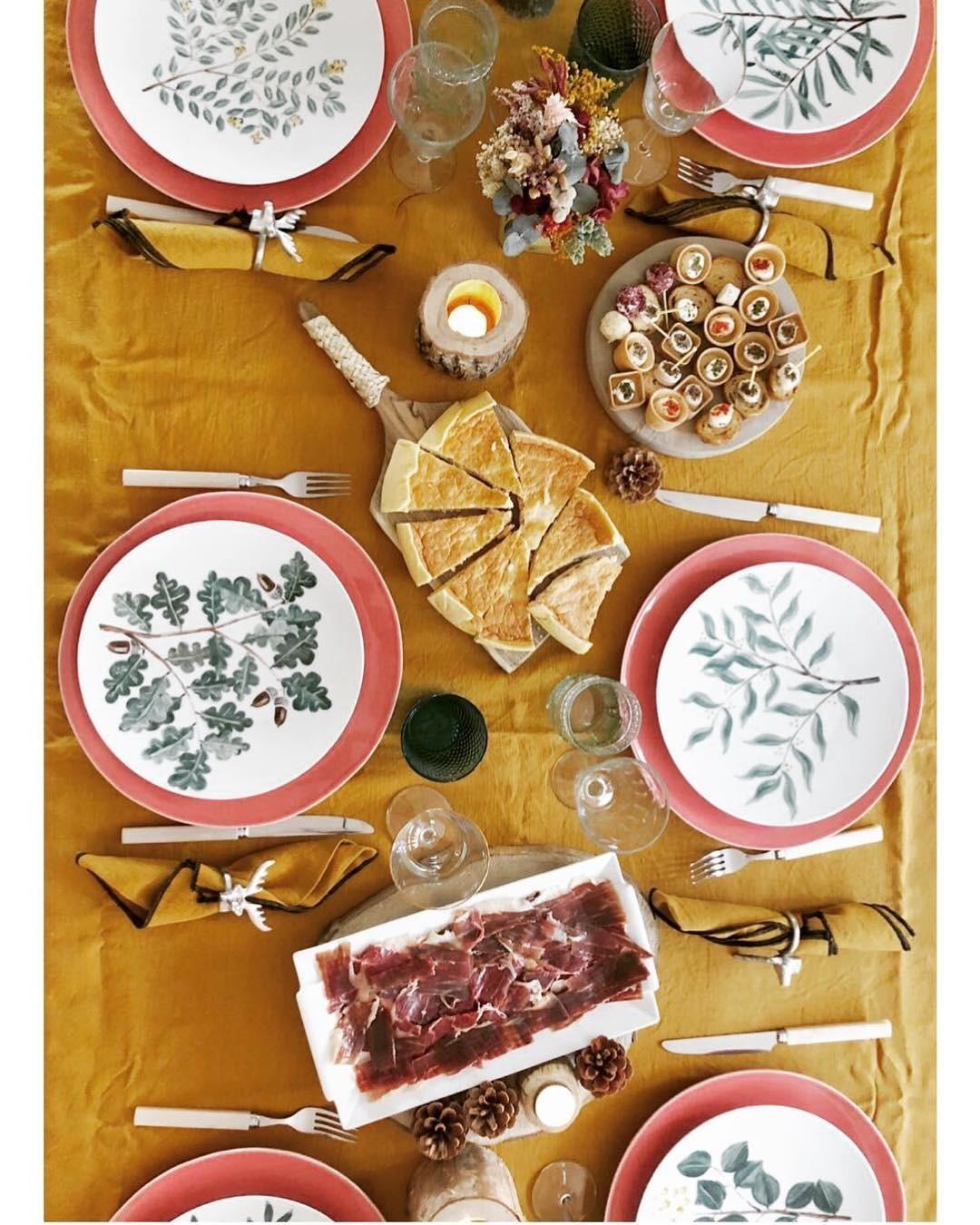 Яркая оранжевая скатерть прекрасно сочетается с красной посудой и мясной нарезкой, а также растительными мотивами на тарелках.