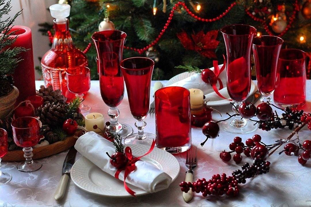 Красные ягоды, посуда глубокого насыщенного и глубокого оттенка, красные бусы и ленточки создают торжественное и праздничное настроение.