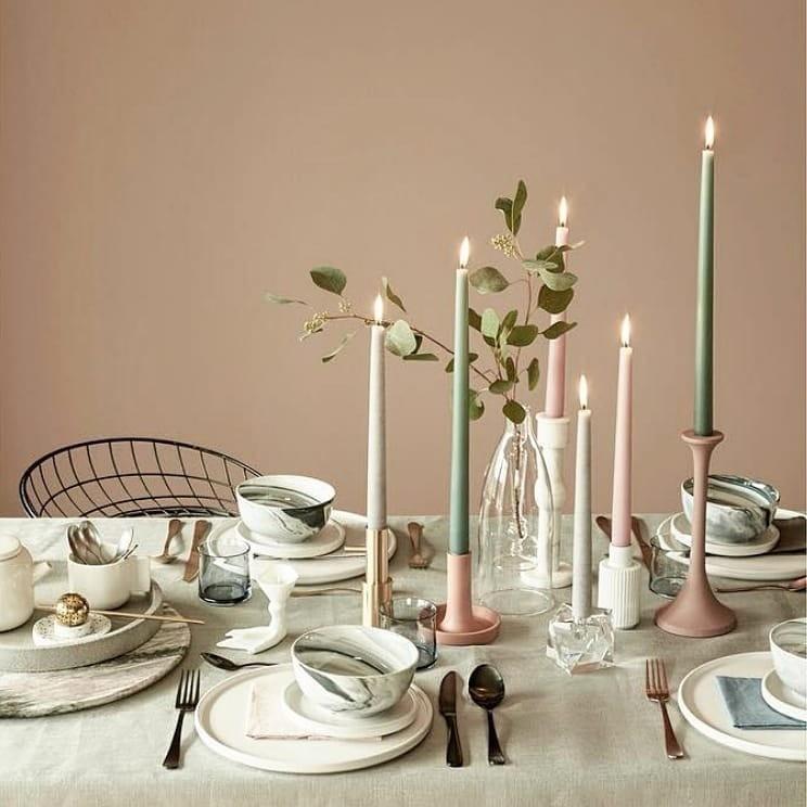 Еще один вариант неожиданного для Нового года цветового решения. Новогодней стол дополнен традиционной веточкой омелы. Основное украшение — посуда с разводами под мрамор и тонкие свечи.