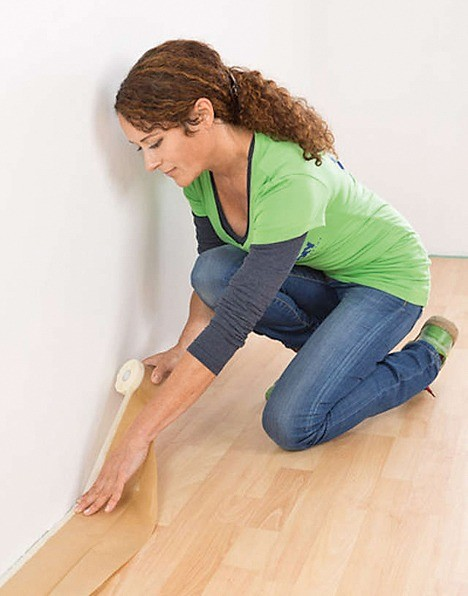 Малярным скотчем защищают края напольного покрытия по периметру комнаты