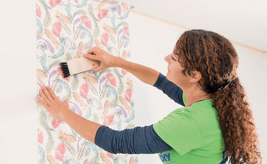 Начиная с угла комнаты, обои прикладывают к стене и разглаживают мягкой щёткой