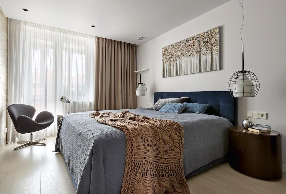 Мягкие цветовые нюансы и тактильно приятные фактуры искусно оттеняют монохромную основу хозяйской спальни. Доминантой композиции служит массивная кровать с бархатным изголовьем цвета коба...