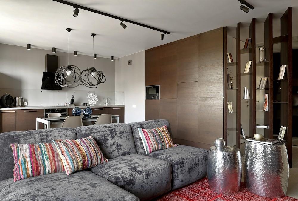 Проницаемый для света стеллаж отделяет гостиную от прихожей, не перегружая при этом пространство, а также является своеобразной витриной для книг и аксессуаров. Его мощные вертикали развё...
