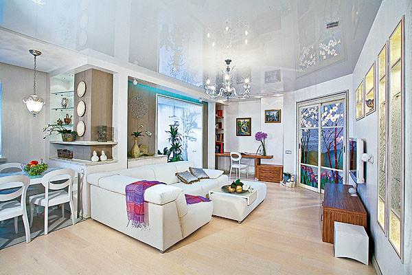 Ахроматическую палитру квартиры оживили предметы мебели, облицованные шпоном зебрано, серовато-коричневые обои в отделке стены, смежной с лоджией, напольная доска цвета топленого молока и, конечно, полихромные витражи