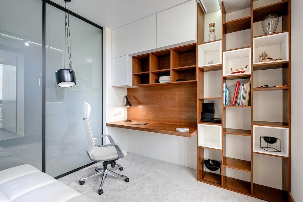В кабинете уголок для работы оформили компактно, стол и навесной стеллаж составляют единую композицию
