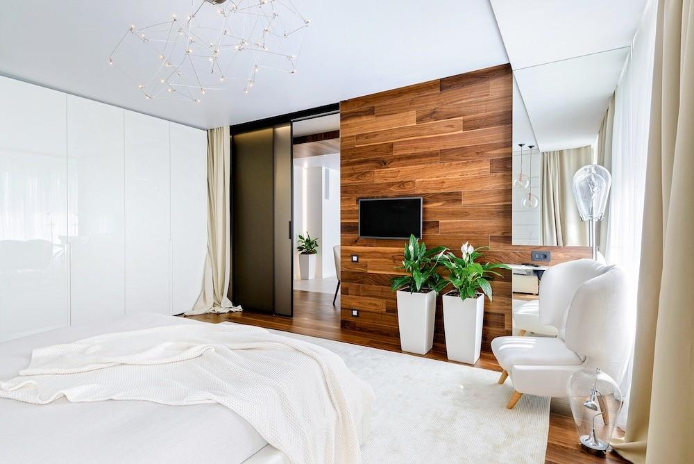 Раздвижные двери позволяют легко объединять спальню со студией. Большой платяной шкаф выглядит как отделанная панелями стена