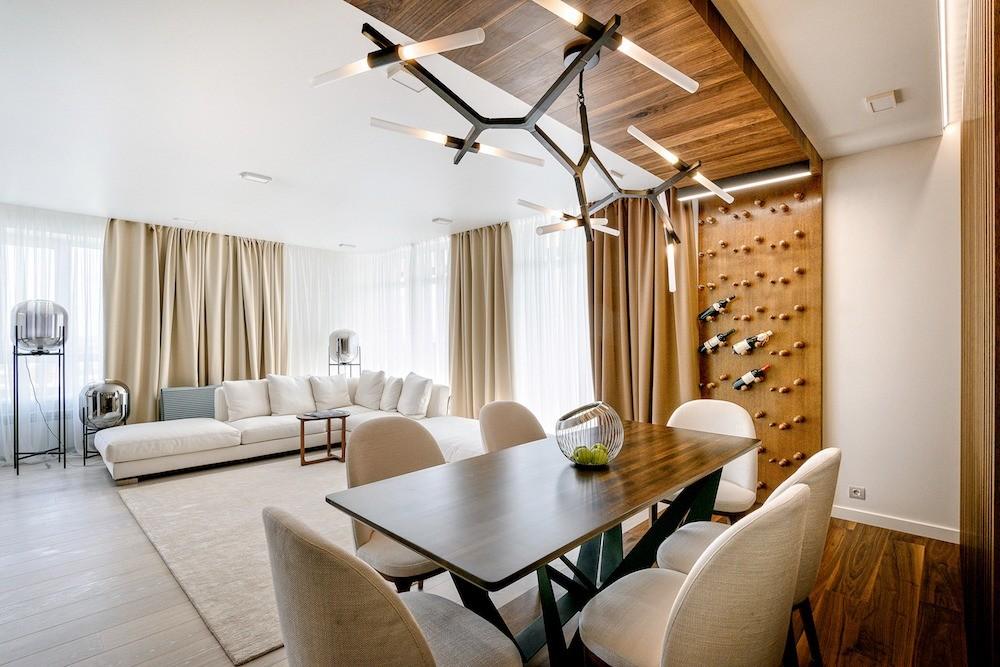 Зона гостиной оформлена на контрасте с обеденной и кухонной, в отделке которых много оттенков дерева. Панель с оригинальным держателем бутылок исполнена по эскизам дизайнера с учётом мало...