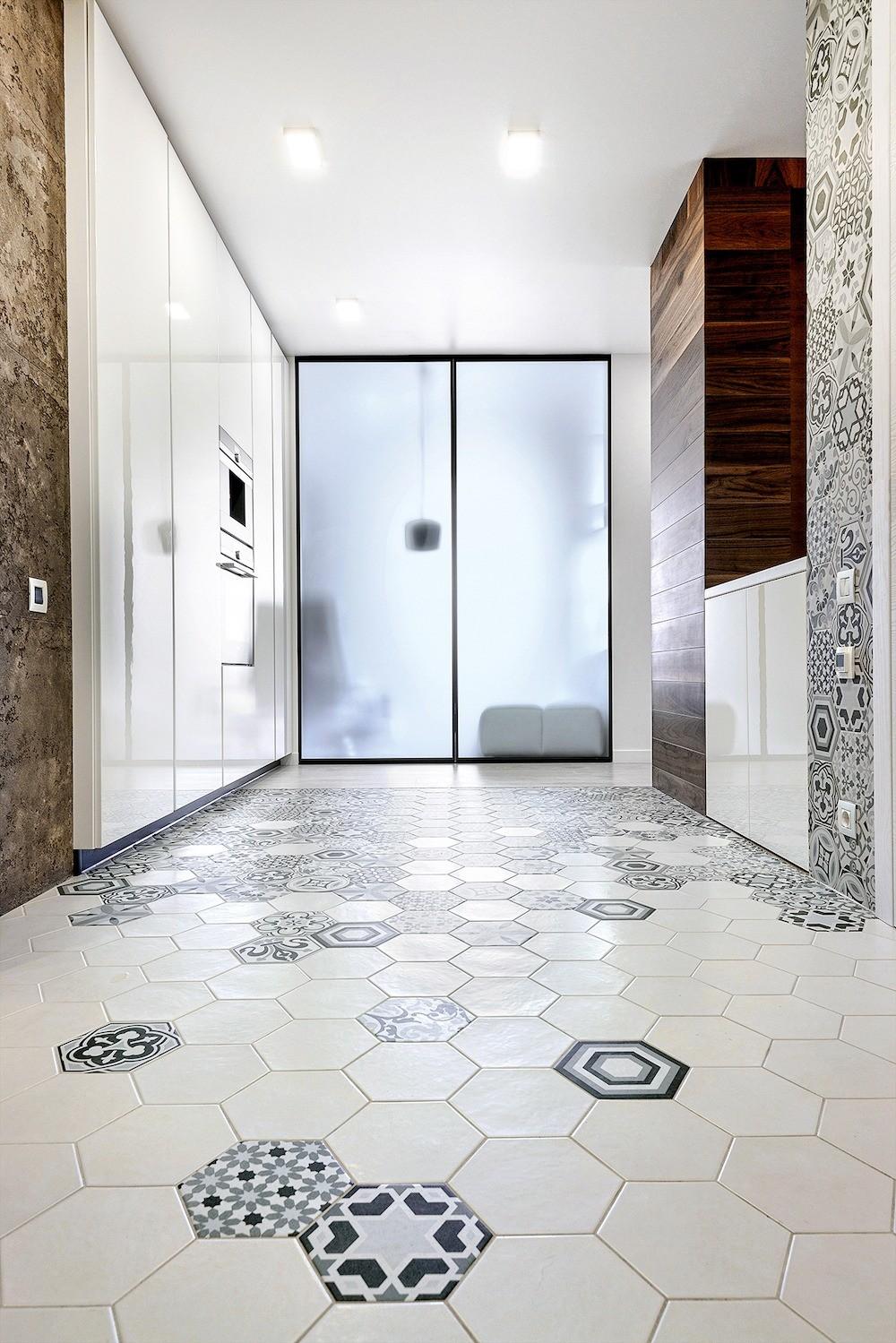 Плитка с графичными узорами украшает пол проходной зоны и один простенок, а также заднюю стену кухонной ниши, объединяя помещения ещё одним лейтмотивом. Светопроницаемые двери способствую...