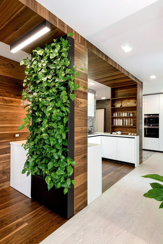 Встроенную бытовую кухонную технику перенесли в зону, соседствующую с прихожей. Вся кухонная мебель изготовлена на заказ по эскизам автора проекта, столешница из искусственного камня