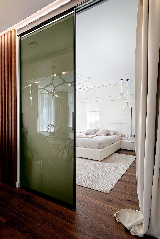 Между студией L-образной формы и прихожей нет преград, а зону гостиной от спальни отделяют раздвижные двери. Семь окон обращены на две стороны света